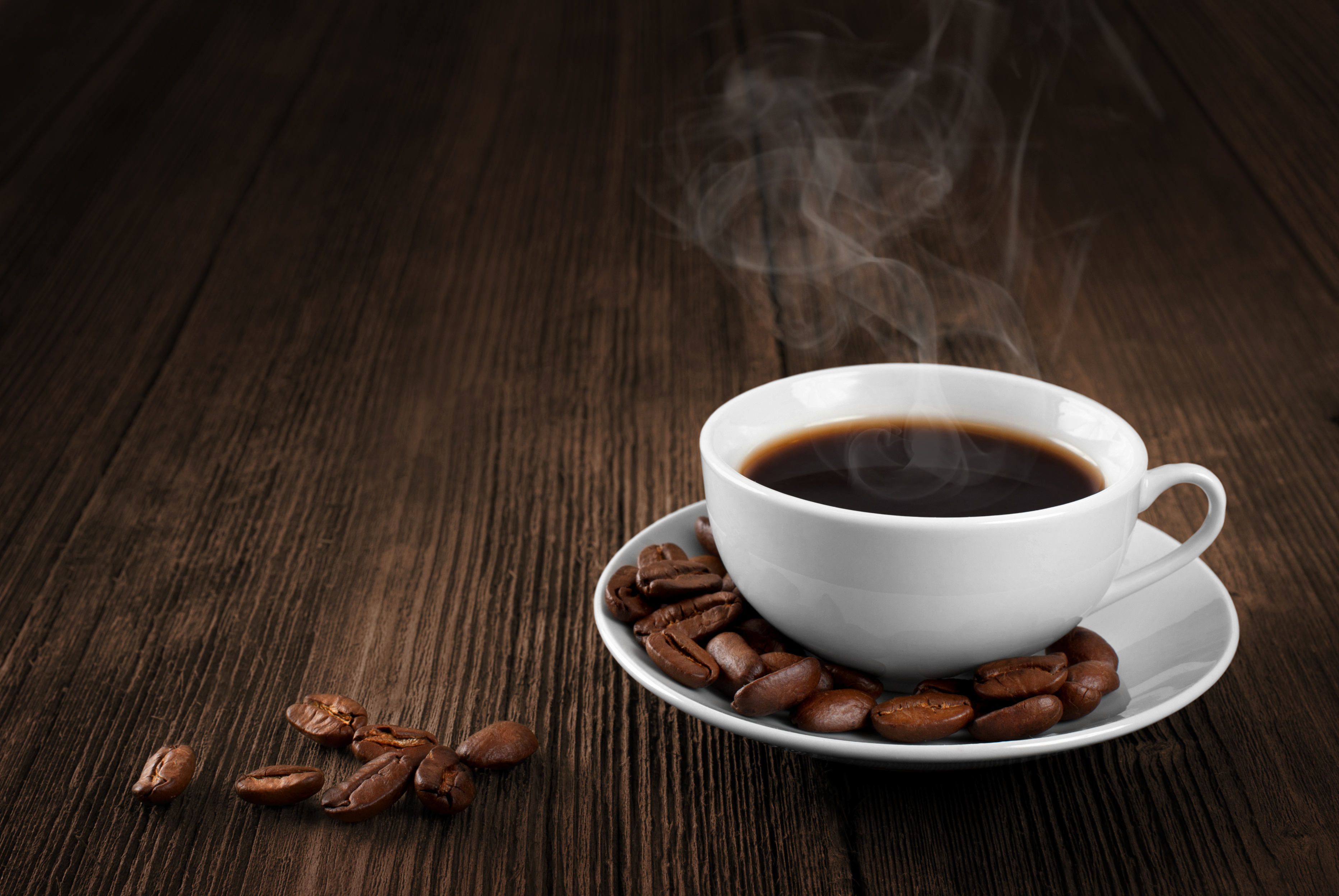 Cup of hot coffee on a wooden table. Coffee beans. Steam.